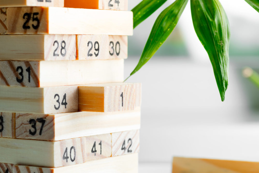 Wooden creative constructor from blocks with numbers against light background. Jenga game for earning, developing and education.
